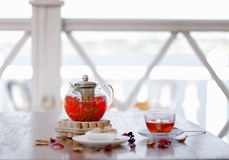 A hot beverage from juicy strawberries and red currant on a table and on a blurred background. Traditional tea ceremony. A tender composition of a transparent Royalty Free Stock Image