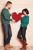 Tender couple in casual clothes,having fun in studio, holding big red heart Royalty Free Stock Photography