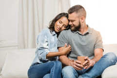 Tender couple with closed eyes hugging on sofa at home Stock Photo