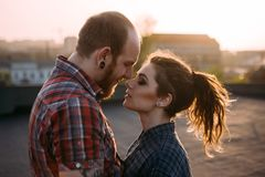 Tender couple cuddle. Relationships background. Passion young people together on roof closeup, atmospheric backlight with focus on foreground, love on top of Stock Photo