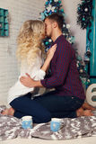 Tender couple in elegant clothes,sitting beside Christmas tree at cozy home Stock Photos