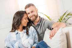 Tender couple embracing and resting on sofa at home Royalty Free Stock Image