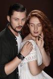 Tender couple posing for studio shot,  on brown Stock Image