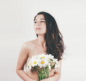 Tender cute beautiful summer young girl with topless body perfect skin. holds camomiles flowers. white background Stock Photos