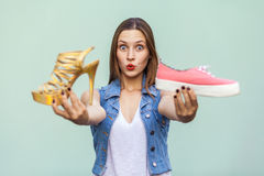 The tender and cute teenage girl with freckles got choosing sneakers or high heels, looking at camera with wonder face. Stock Images
