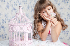 Tender dreamy romantic girl near open birdcage. Portrait of tender sincere dreamy romantic openhearted blond girl with long wavy hair looking at flower seating Royalty Free Stock Images