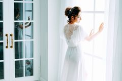 Tender elegant young bride with hairdo, hairpin and bridal makeup. Tender elegant young brunette bride with hairdo, hairpin and bridal makeup wearing white stock images