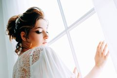 Tender elegant young bride with hairdo, hairpin and bridal makeup. Tender elegant young brunette bride with hairdo, hairpin and bridal makeup wearing white royalty free stock photography