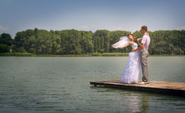 Tender embracing. The groom holds the bride in handson a jetty Stock Photo