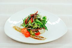 Tender exquisite salad with turkey melange sun-dried tomatoes and greens in a white plate on a white tablecloth.  Stock Photos
