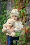 Tender feelings of autumn times. Little girl against the backdrop of autumn leaves and the stone wall hugging a soft toy Royalty Free Stock Photos