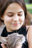Tender friendship. Young beautiful dark-haired girl with tabby cat Royalty Free Stock Photo