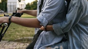 Tender, gentle cheek kiss from a young woman to her boyfriend. Couple are sitting on a bike in the park. Wearing trendy. Similar clothes stock footage