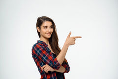 Tender girl dressed in plaid shirt smiling and pointing finger. Stock Image
