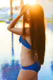 Tender girl enjoying summer sun. Tender girl enjoying summer sun in blue bikini near the pool Royalty Free Stock Image