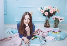 Tender girl lying on the floor, eating macarons. Tulip flowers on the blue wall background in the spring morning royalty free stock photography