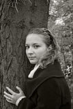 Tender girl near a dark tree trunk Royalty Free Stock Photo