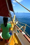 Tender girl on yacht with red sails looks ahead stock image