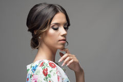 Tender glamorous beauty with finger on chin and bun hairstyle looking down Royalty Free Stock Photos
