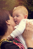 Tender grandmother with baby. Grandmother holding and kissing tenderly her granddaughter. Warm effect edition Royalty Free Stock Photos