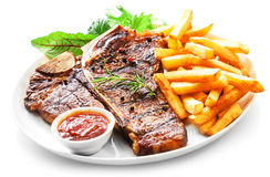 Tender grilled porterhouse or t-bone steak. Served with crisp golden French fries and fresh green herb salad accompanied by a BBQ or tomato ketchup sauce Royalty Free Stock Image