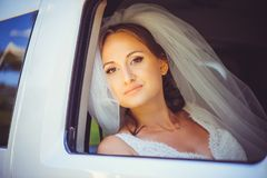 Tender happy bride in the car, happy woman in a wedding dress looking out the window, white veil on her head royalty free stock photo