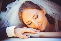 Tender happy bride in the car, a happy woman in a wedding dress laying her head on the arm of the mozhchina, white veil on her hea Royalty Free Stock Photo