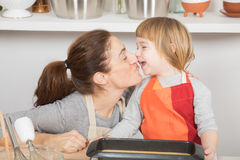 Tender and happy mother and child when finishing cake Stock Photos