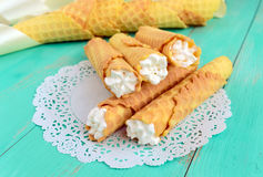 Tender honey wafers in the form of tubes, stuffed with air cream on white lace napkin. Royalty Free Stock Photos