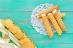Tender honey wafers in the form of tubes, stuffed with air cream on white lace napkin. Royalty Free Stock Photo