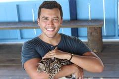 Tender human holding baby wild feline.  royalty free stock photo
