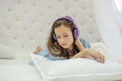 Tender innocent girl listening to music with headphones lying on white bed. Tender innocent girl is listening to music with headphones lying on white round  bed Stock Images