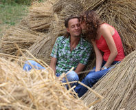 Tender kiss. Young adult caucasian couple laughing and playfully sitting in hay. Attractive man close one's eyes. The curly girl kisses on cheeks of boyfriend Royalty Free Stock Image