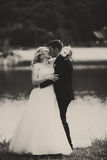 A tender kiss of newlyweds standing on the lake shore Stock Photo