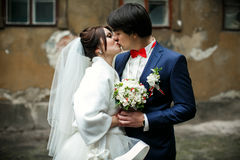 A tender kiss of newlyweds standing on the old gray backyard.  Royalty Free Stock Images