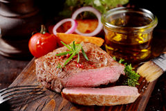 Tender lean medallion of rare grilled beef steak. Seasoned with fresh herbs cut through to show the texture and served with fresh vegetables on a rustic wooden Royalty Free Stock Images