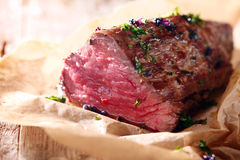 Tender lean rare roast beef. Seasoned with fresh herbs and spices on a piece of oven paper Royalty Free Stock Image