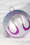Tender lilac Christmas bauble on to snow. Royalty Free Stock Images