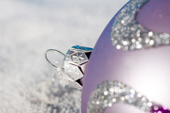 Tender lilac Christmas bauble on to snow. Stock Photo
