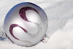 Tender lilac Christmas bauble on to snow. Royalty Free Stock Photo