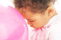 Tender little girl with a pink balloon. Close-up portrait of a tender little girl with a pink balloon Royalty Free Stock Image