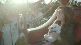 Jolly girl rides on a roundabout and hugs her teddy bear happily in a park in autumn in slo-mo stock footage