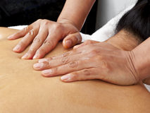 Tender massage. Hands of massage therapist pressing woman's back Stock Photo