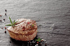 Tender medallion of fillet or rump steak. Tender medallion of lean grilled fillet or rump steak seasoned with salt and peppercorns and garnished with fresh Stock Images