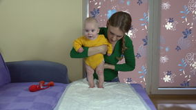 Tender mom with cute baby girl make squat exercises. 4K stock footage