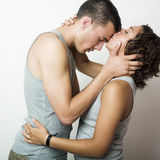 A tender moment. Intimate portrait of a young couple in love. She is kissing her tenderly on the forehead Royalty Free Stock Photos