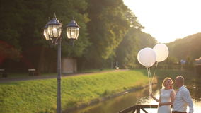 Tender moment of happiness and love. Young beautiful wedding couple with balloons embracing on the bridge sunset river stock footage