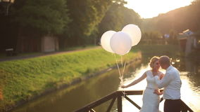 Tender moment of happiness. Young beautiful wedding couple with balloons embracing on the bridge sunset river on stock video footage