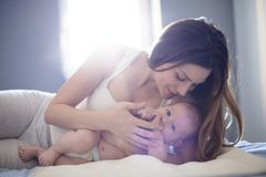Tender moments with mom. Mother and baby on bed. Copy space royalty free stock photos