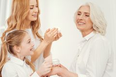 Tender mother and daughter taking care of beautiful grandmother. Harmonious family relationships. Side view on full of love mature lady and her little daughter Royalty Free Stock Image